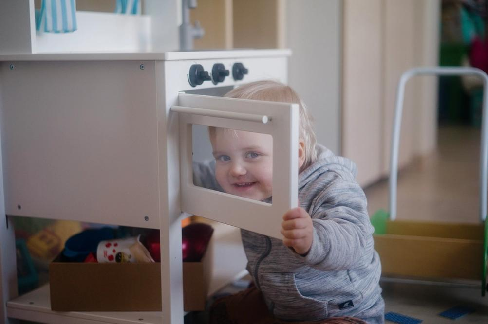 Photo of a small boy looking through a toy oven window.