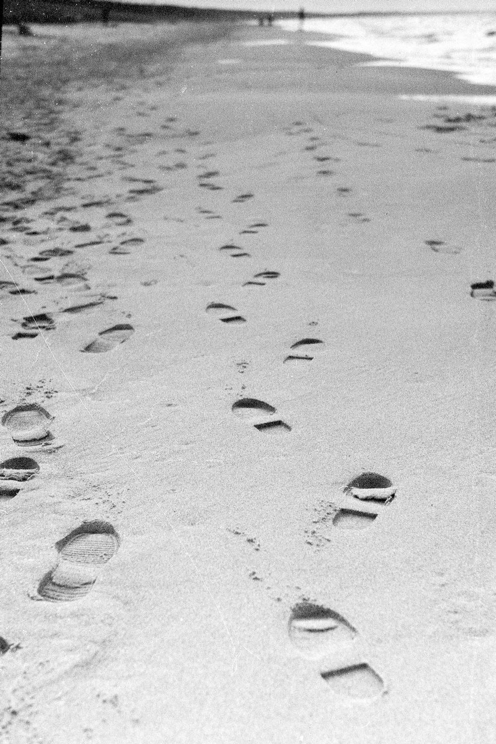 Photo of foot marks in the sand.