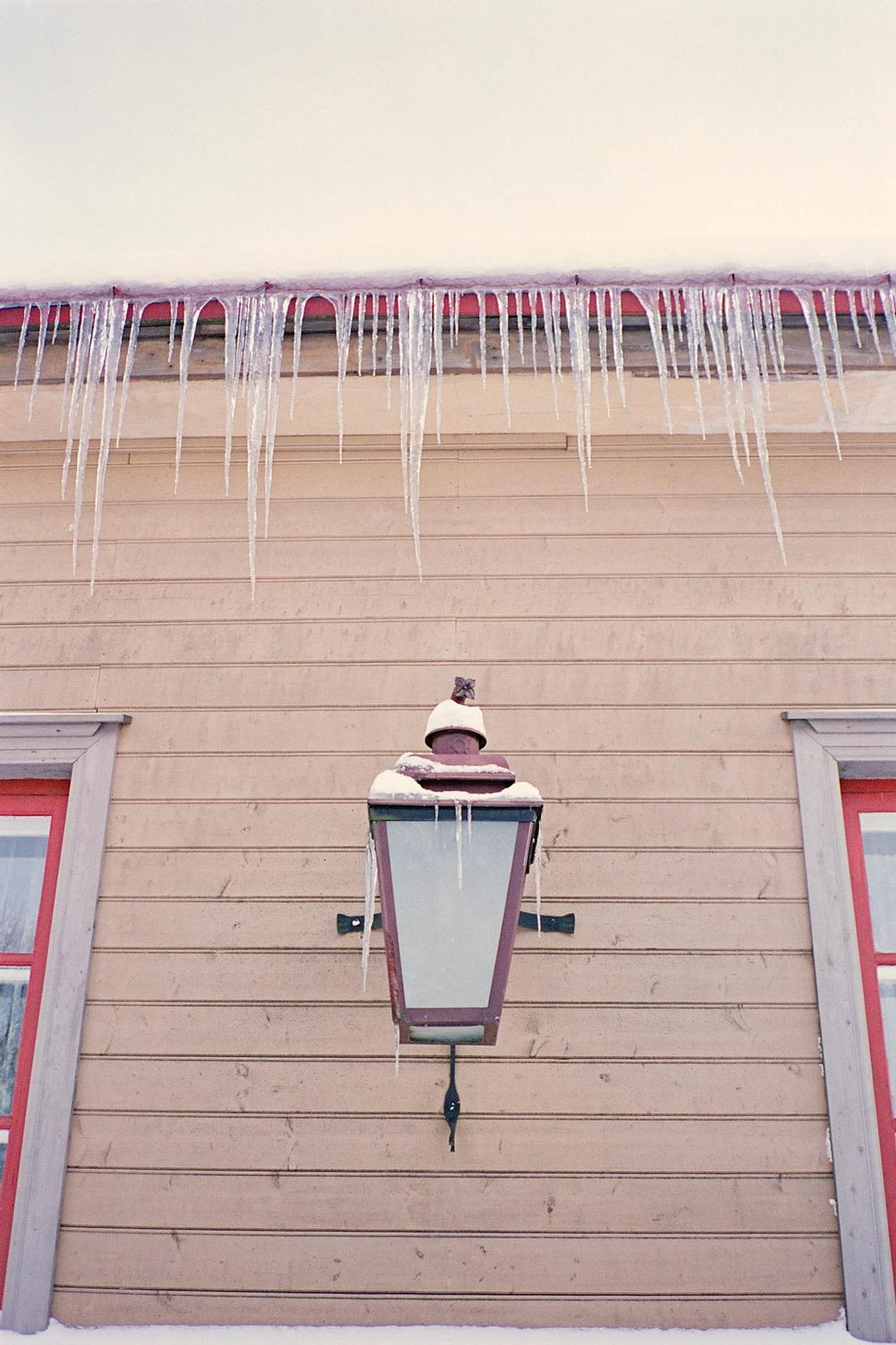 Closeup of a house with window corners, lamp and frozen water.