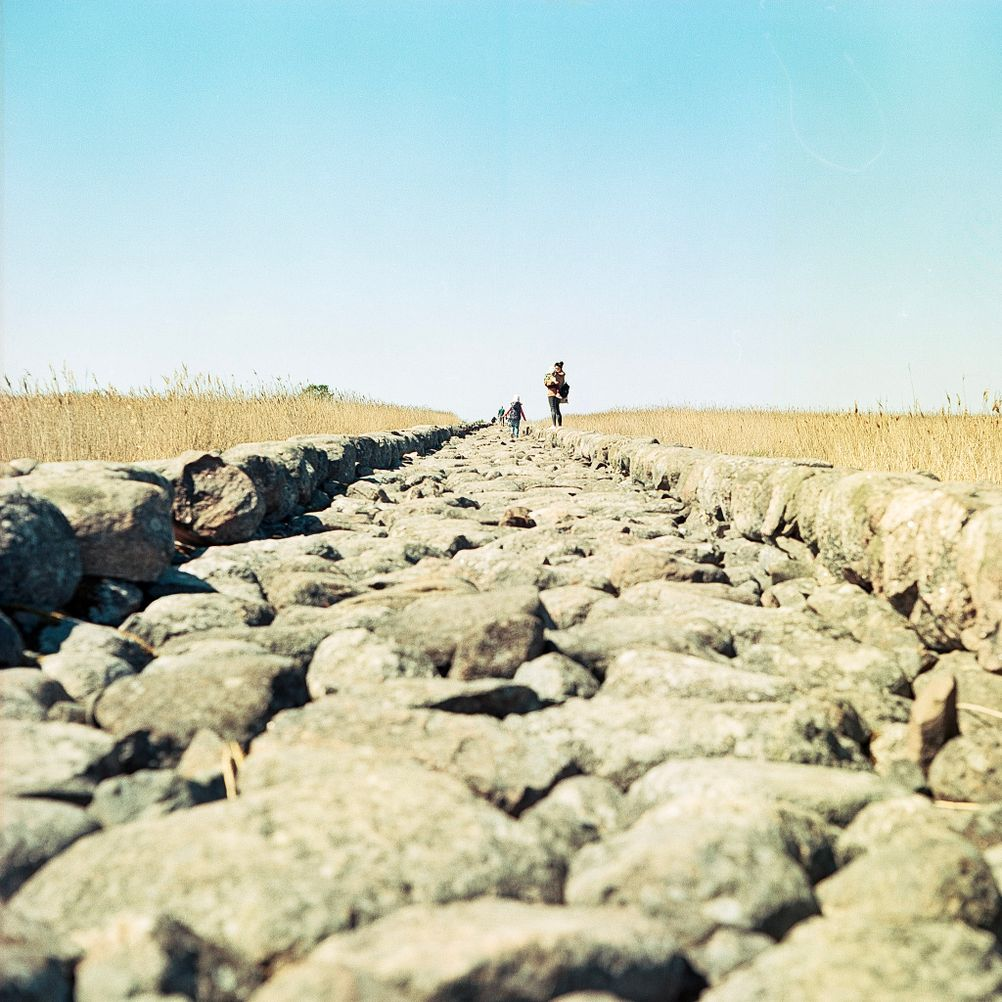 Photo of a path made from rocks towards the sea.