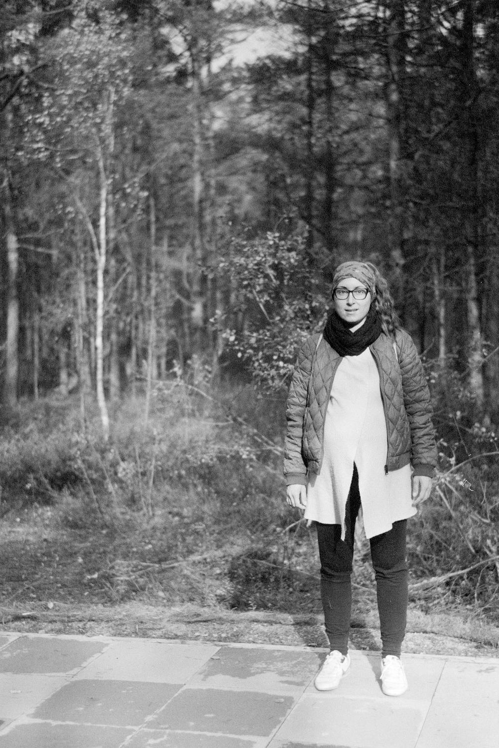 Photo of my wife standing in forest.