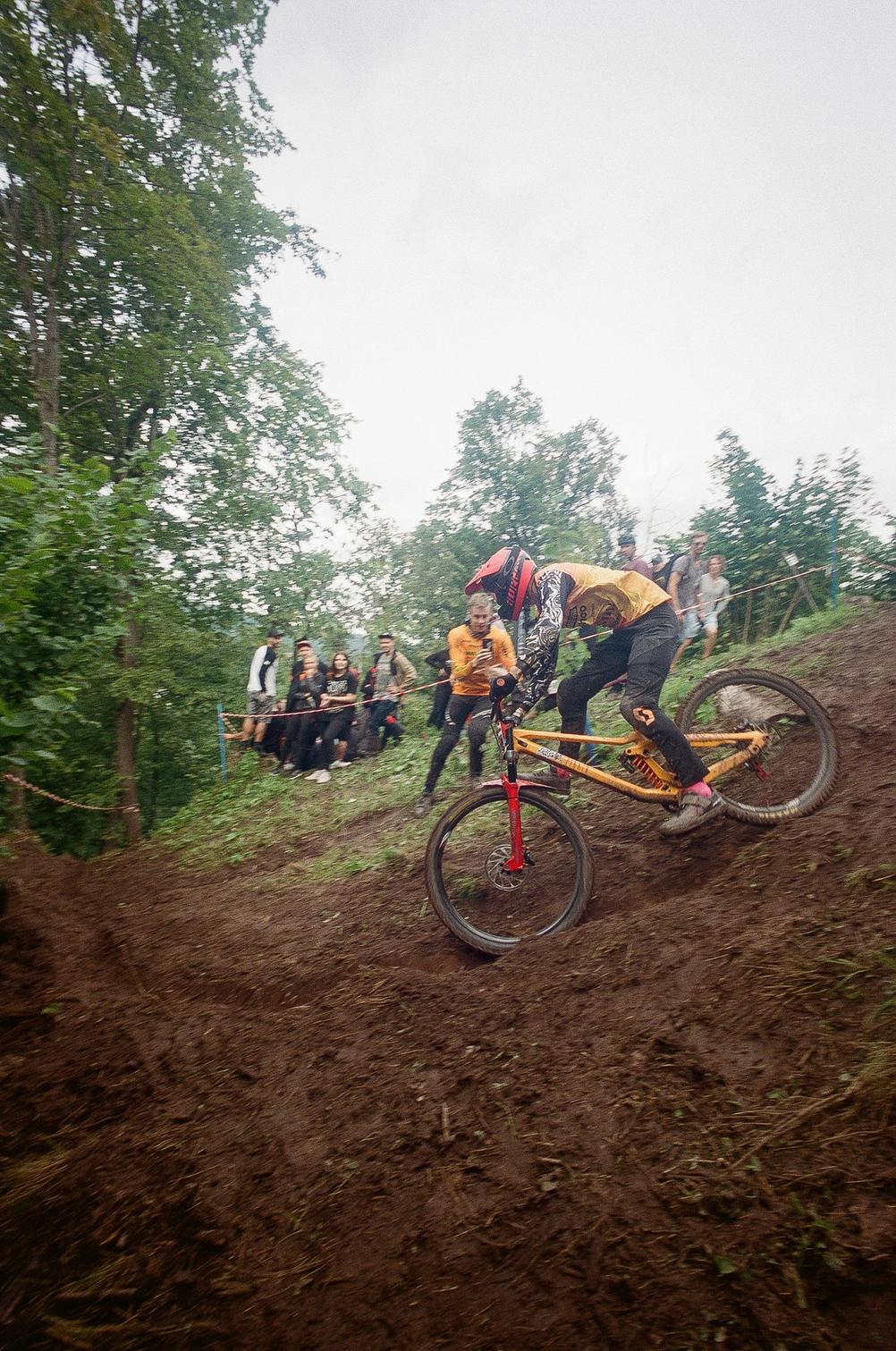 Downhill racer about to ride a natural berm it wet conditions.