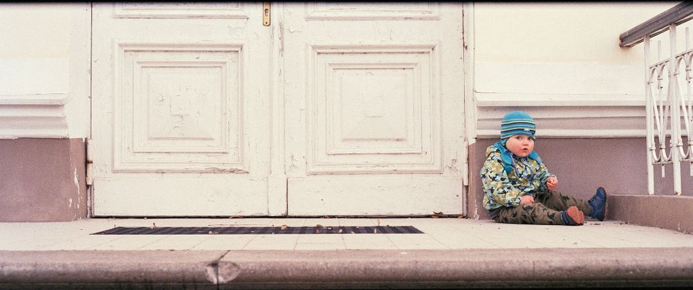 Photo of my son sitting next to some door.