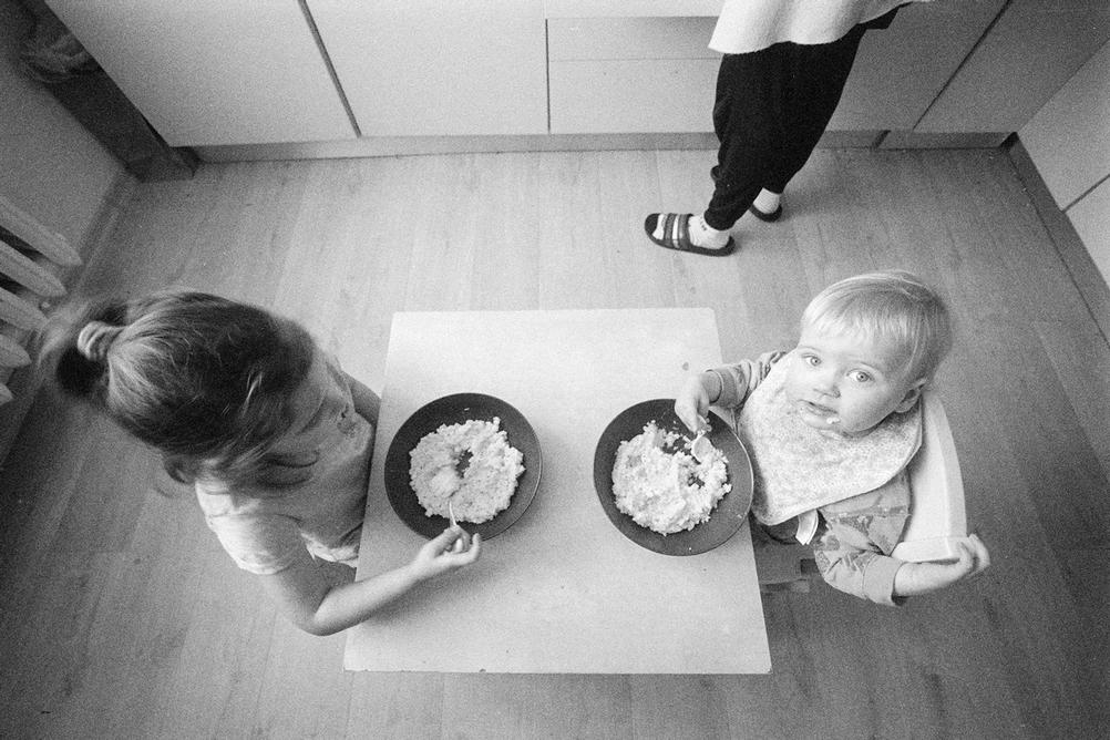 Photo of brother and sister eating breakfast.