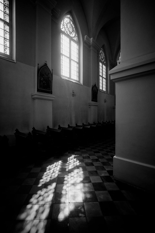 Photo of sun shining through church window on ground.