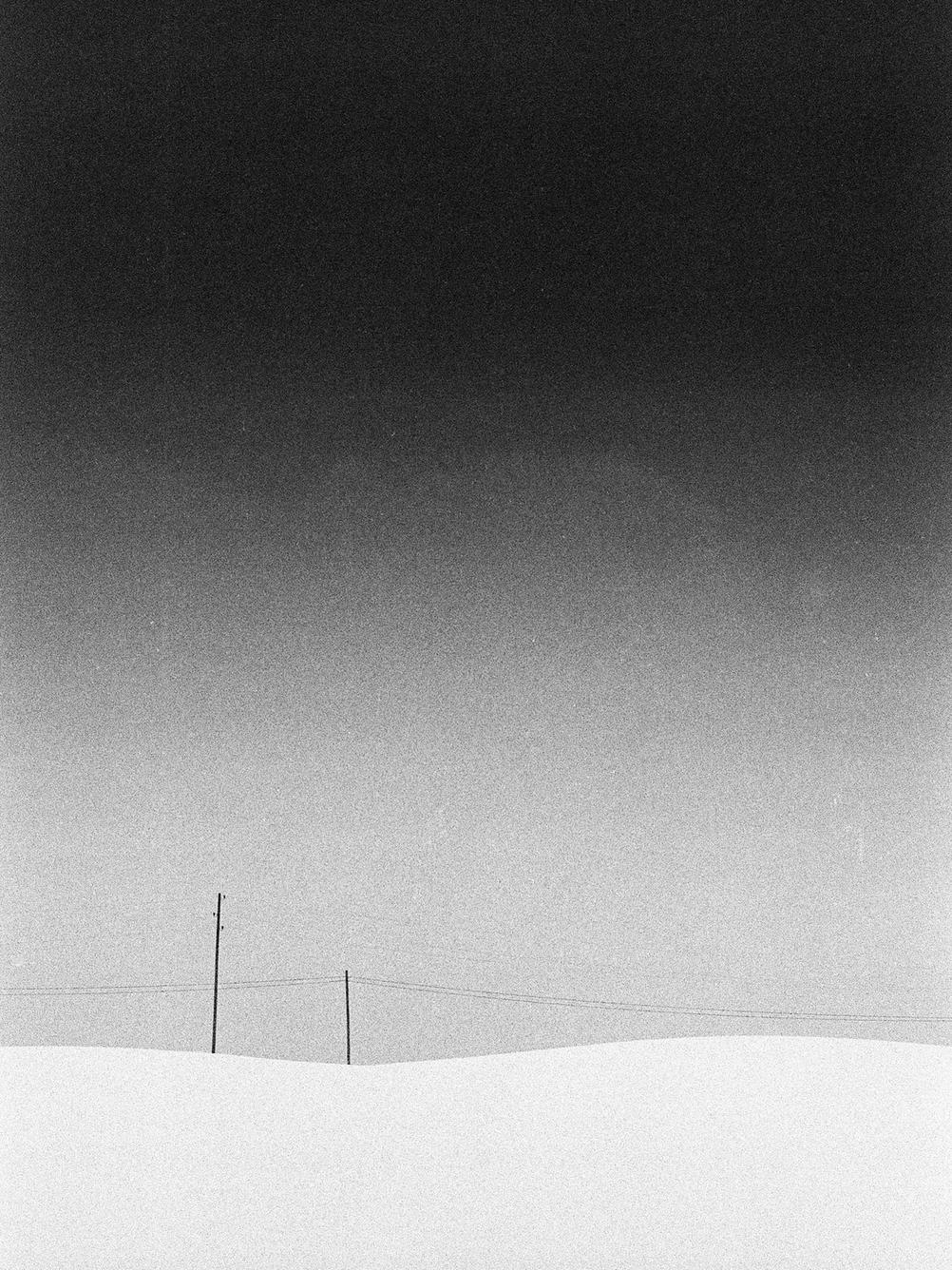 Minimalist photo of two electricity poles in the snow.