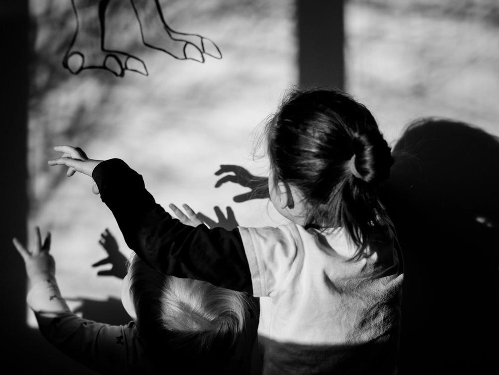 Photo of children acting like dinosaurs.