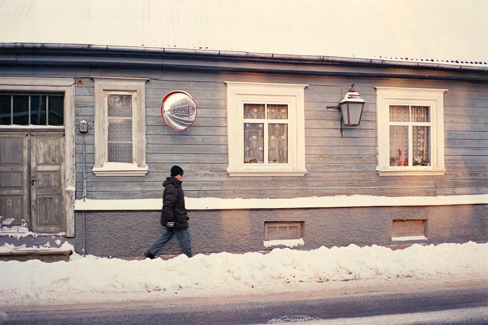 Photo of a man walking on street.