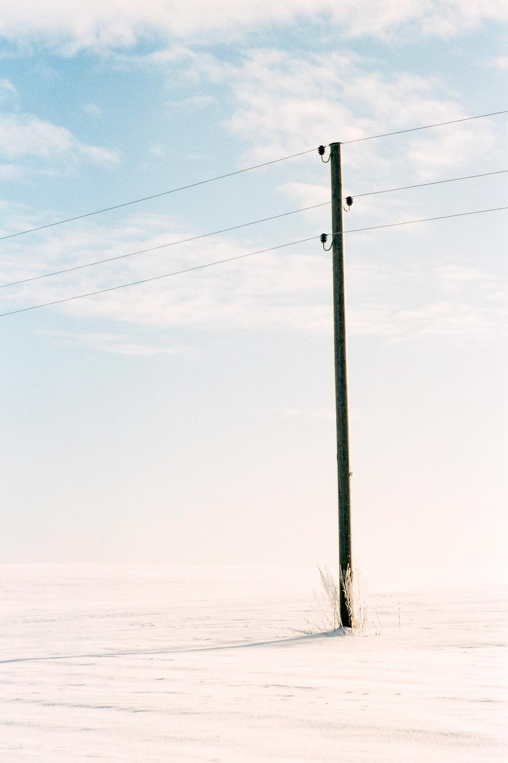 Photo of a lone pole in a field.