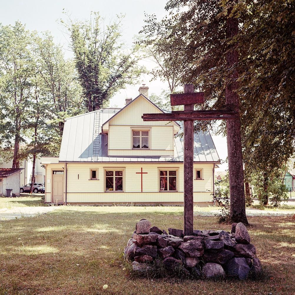Photo of a big cross in front of a house with another cross.
