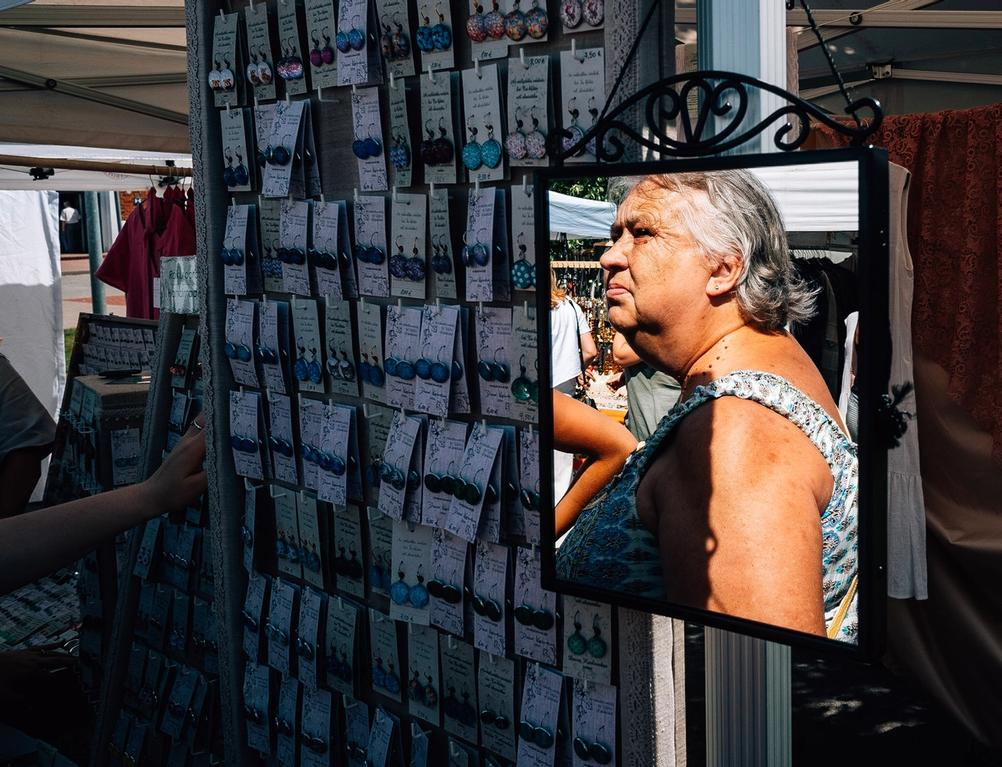 Photo of an older women looking at earrings in market.