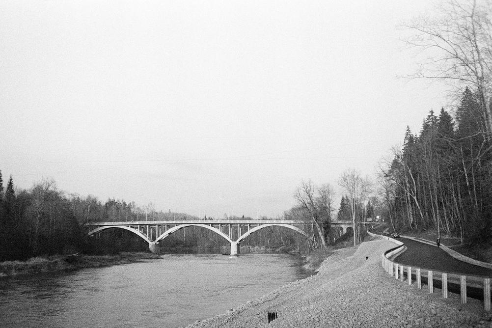 Black and white photo of a bridge across river.