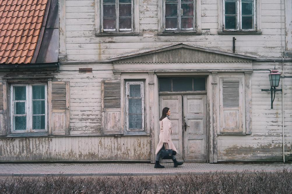 Photo of a woman walking next to house.