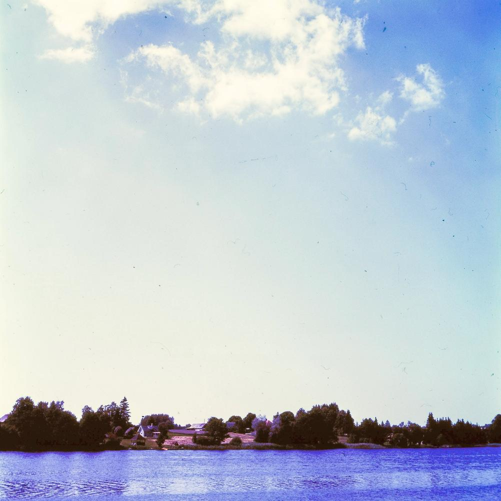 Photo of a distant house next to a lake.
