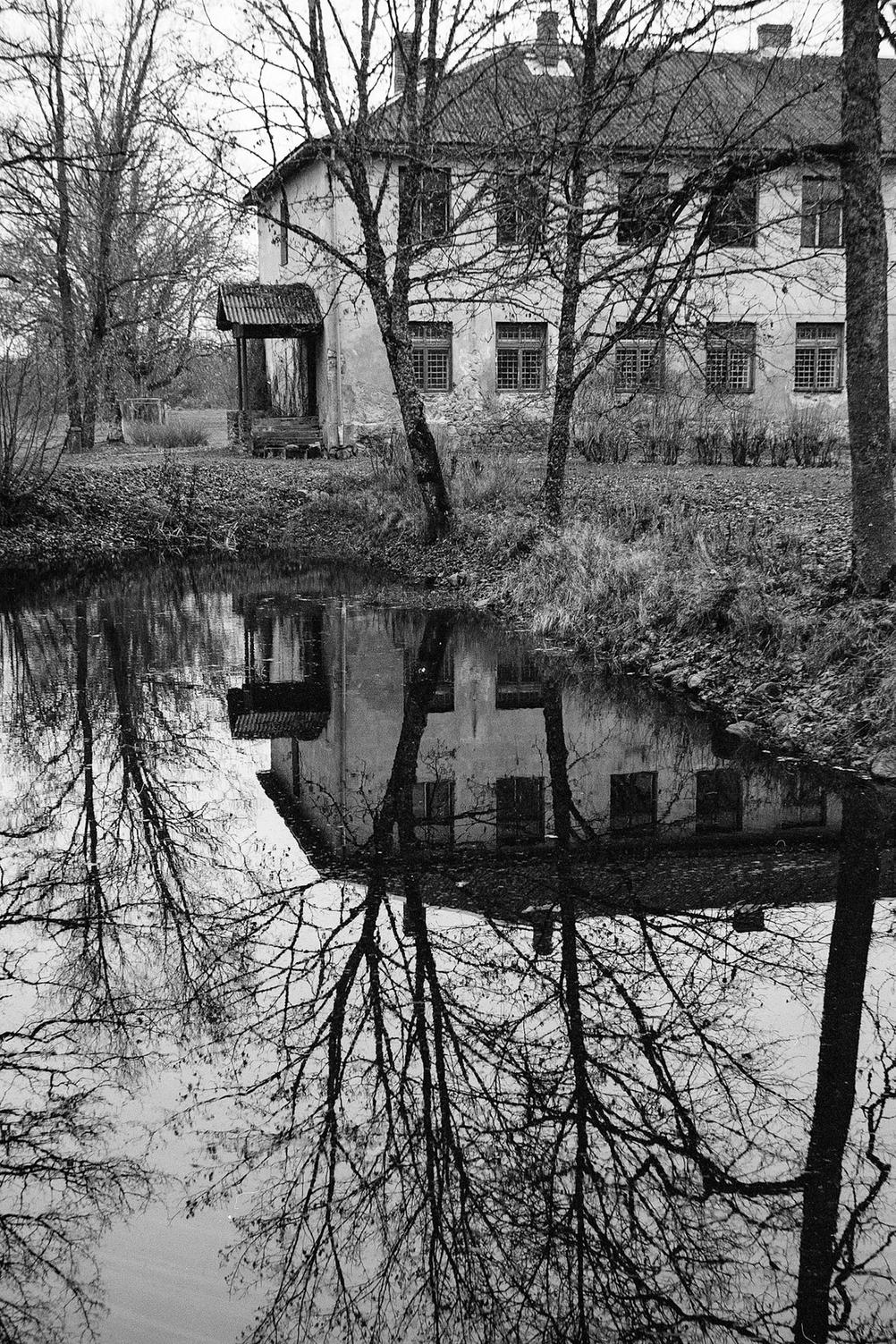 Photo of a house and a tree and their reflection in a pond.