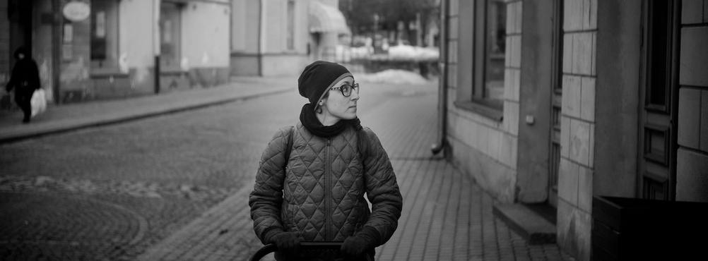 Photo of a women looking around city.