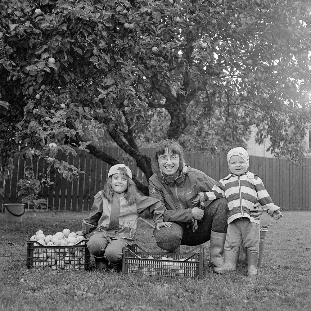 Photo of my family next to many apples.