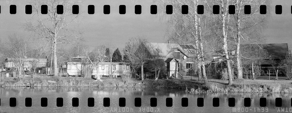 Black and white photo of some houses next to water.