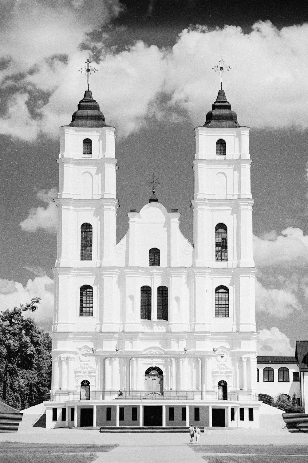 Photo of a white church in front of slightly dramatic clouds.