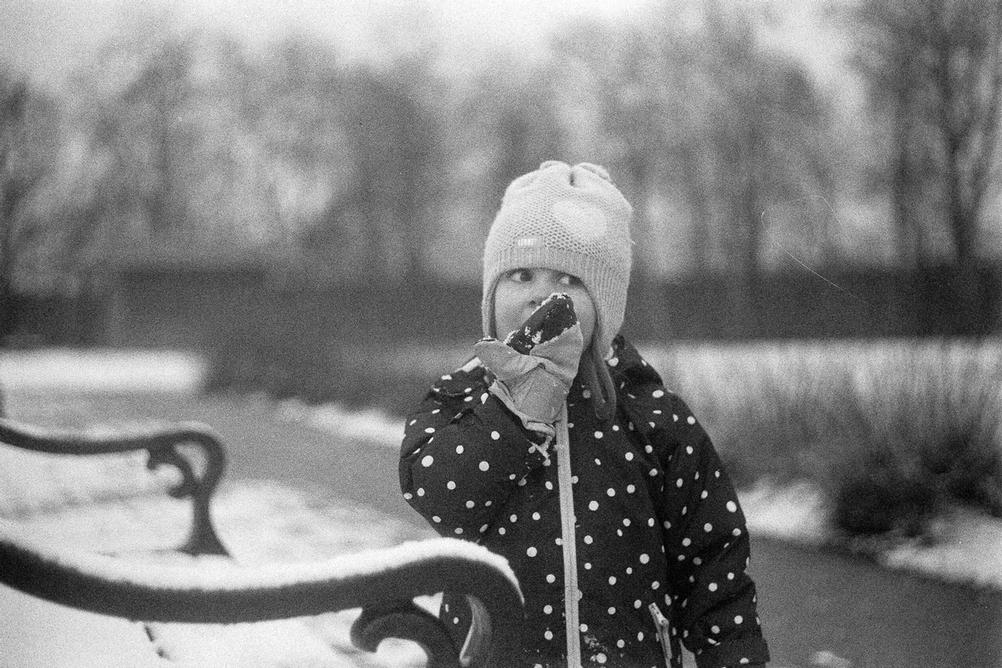 Photo of a young girl eating snow.