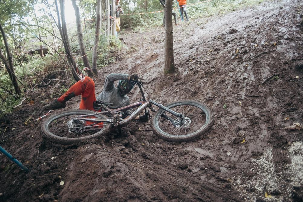 Downhill racer crashing in mud during training.