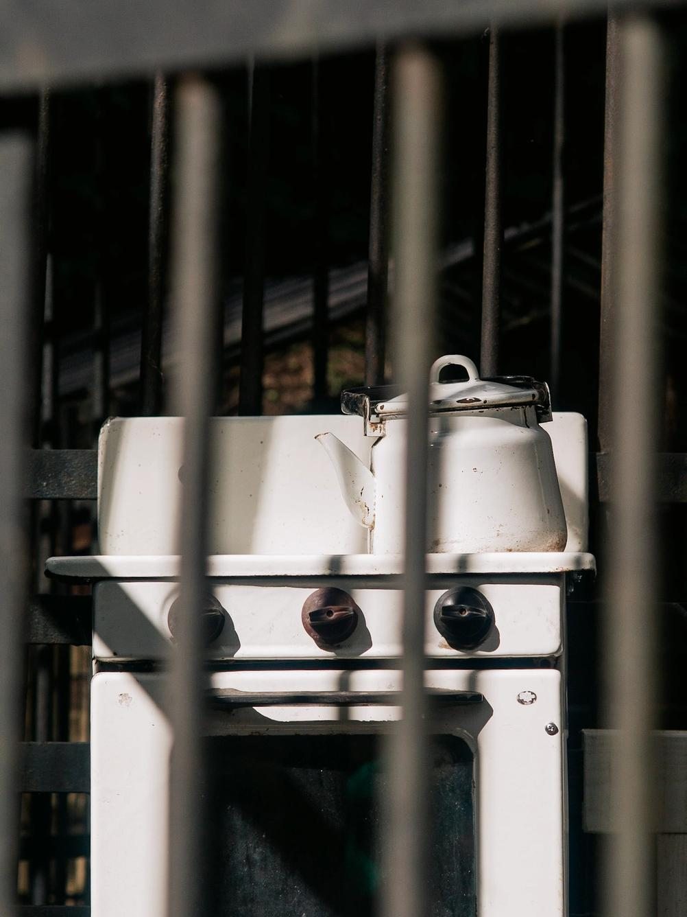 Photo of an old kitchen equipment taken through some bars.