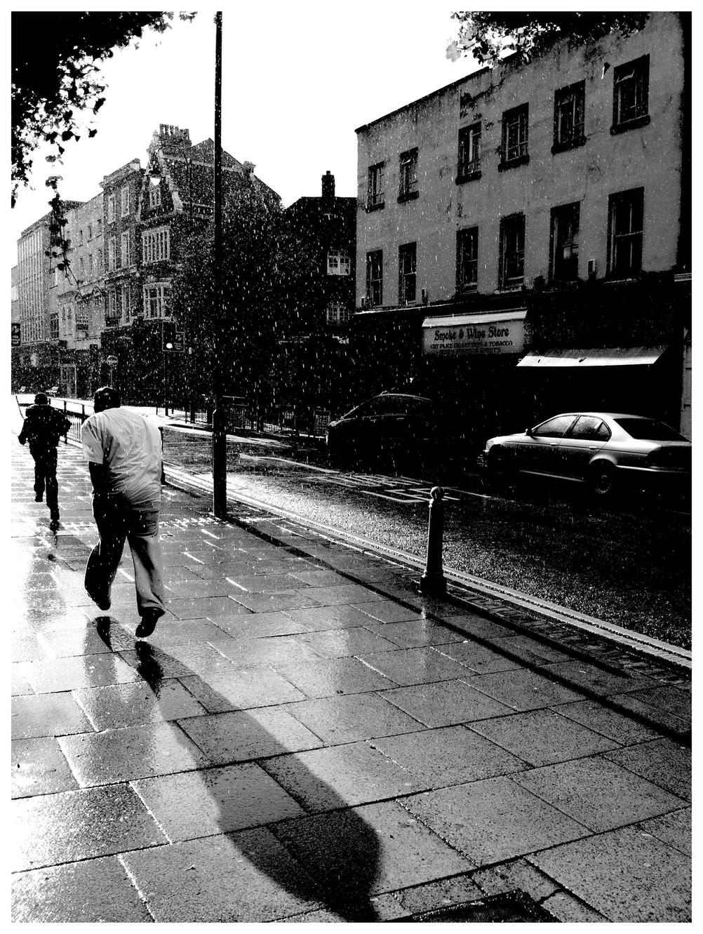 Photo of people running from rain.