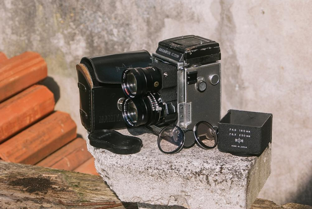 Photo of Mamiya C220 with Mamiya Super-Sekor 180mm f4.5 lens and accessories.