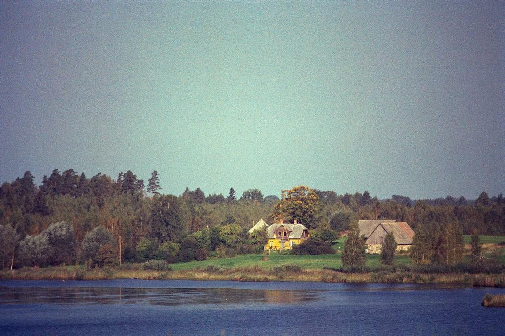 Photo of distant houses next to some water.
