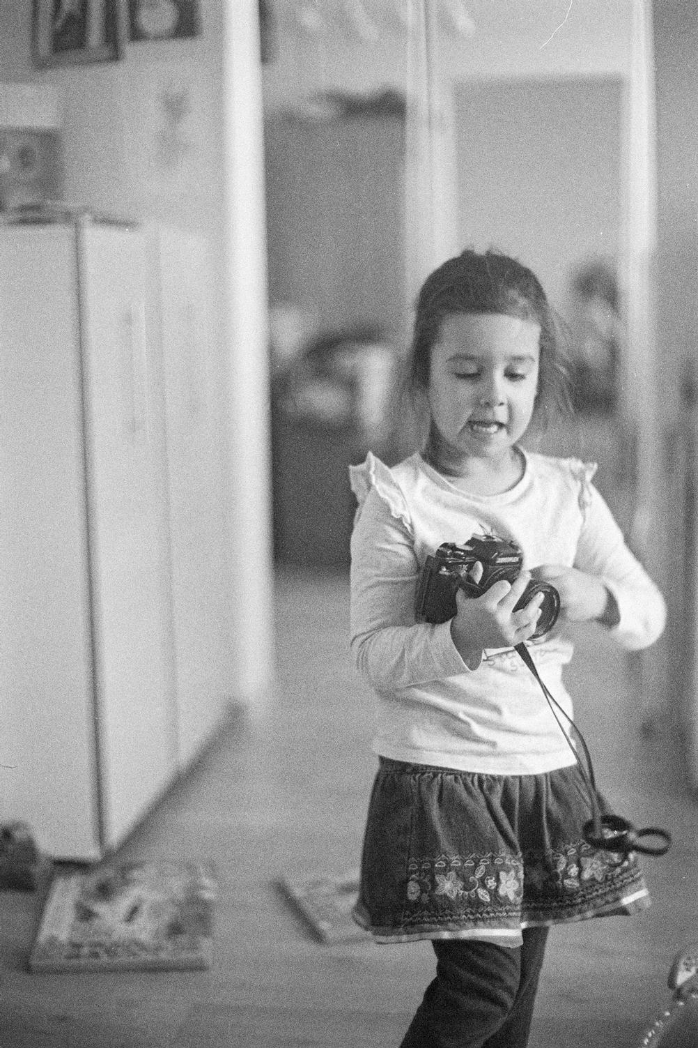 Photo of my daughter holding a film camera.