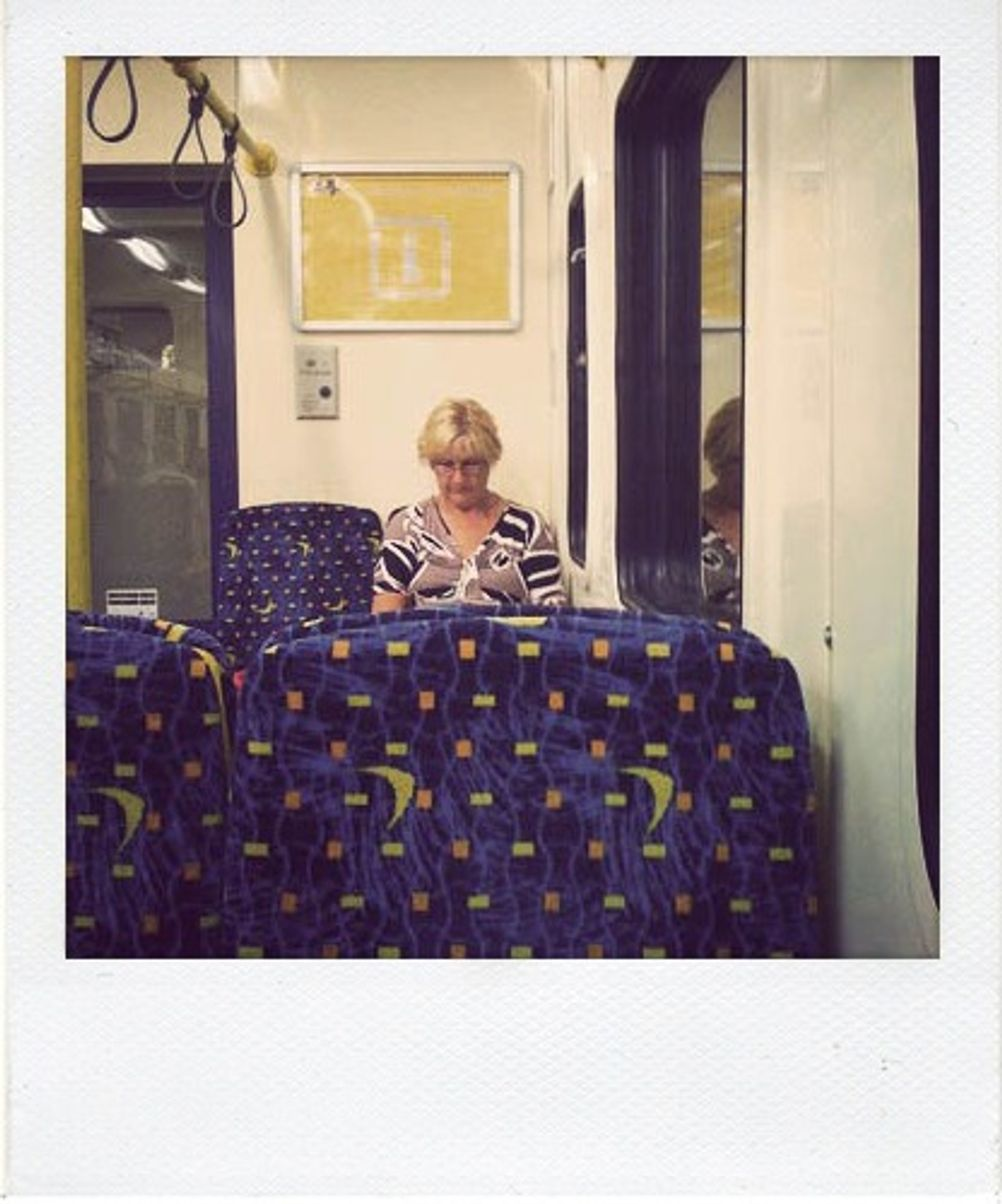 Photo of a woman sitting on a train.