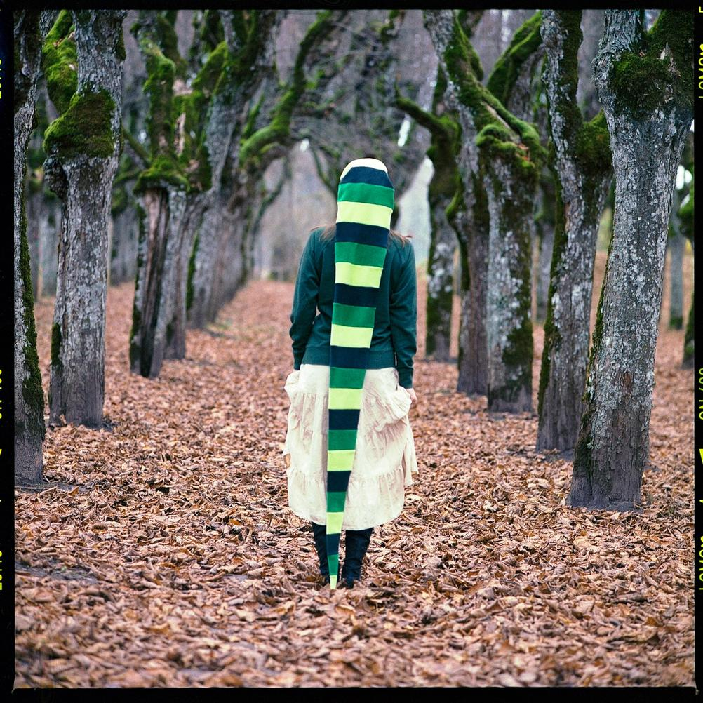 Photo of a women dressed in green between trees.