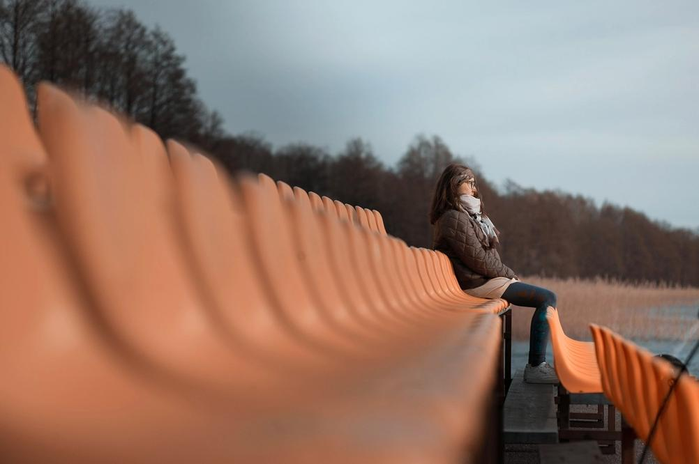 Photo of a woman sitting on some benches.