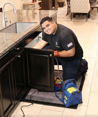 One of our senior plumbers performing drain cleaning services next to the client in Temecula, CA