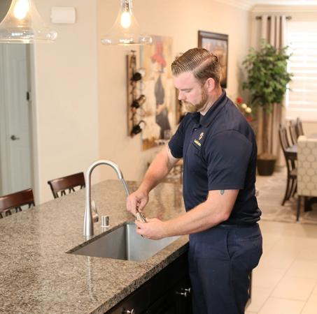 One of our skilled plumbers performing a kitchen faucet replacement for a client in Temecula, CA