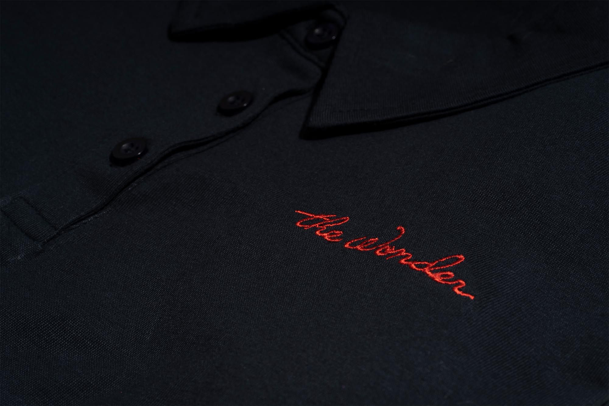 Detail of button down black shirt with logo
