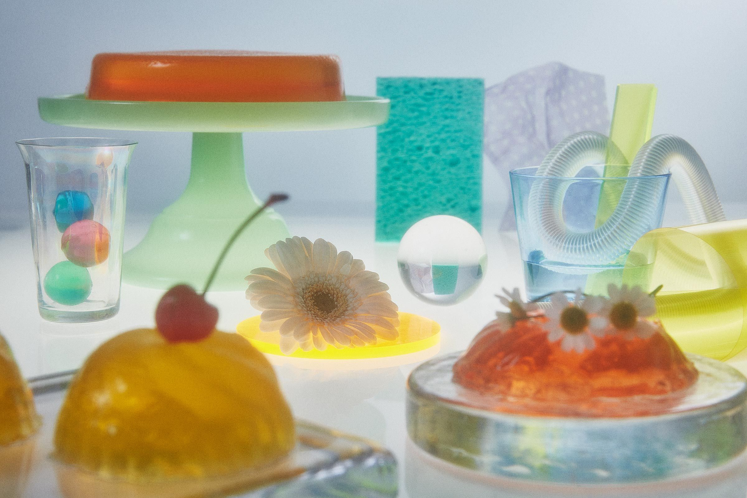 A table packed with flowers, jello, marbles, candy, and plastic samples