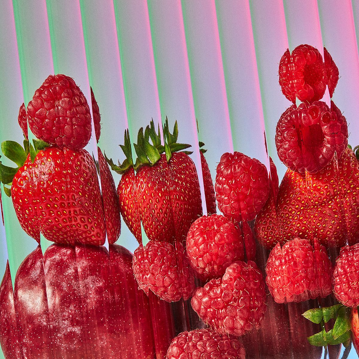 Red strawberries and raspberries stacked on top of each other photographed behind glass