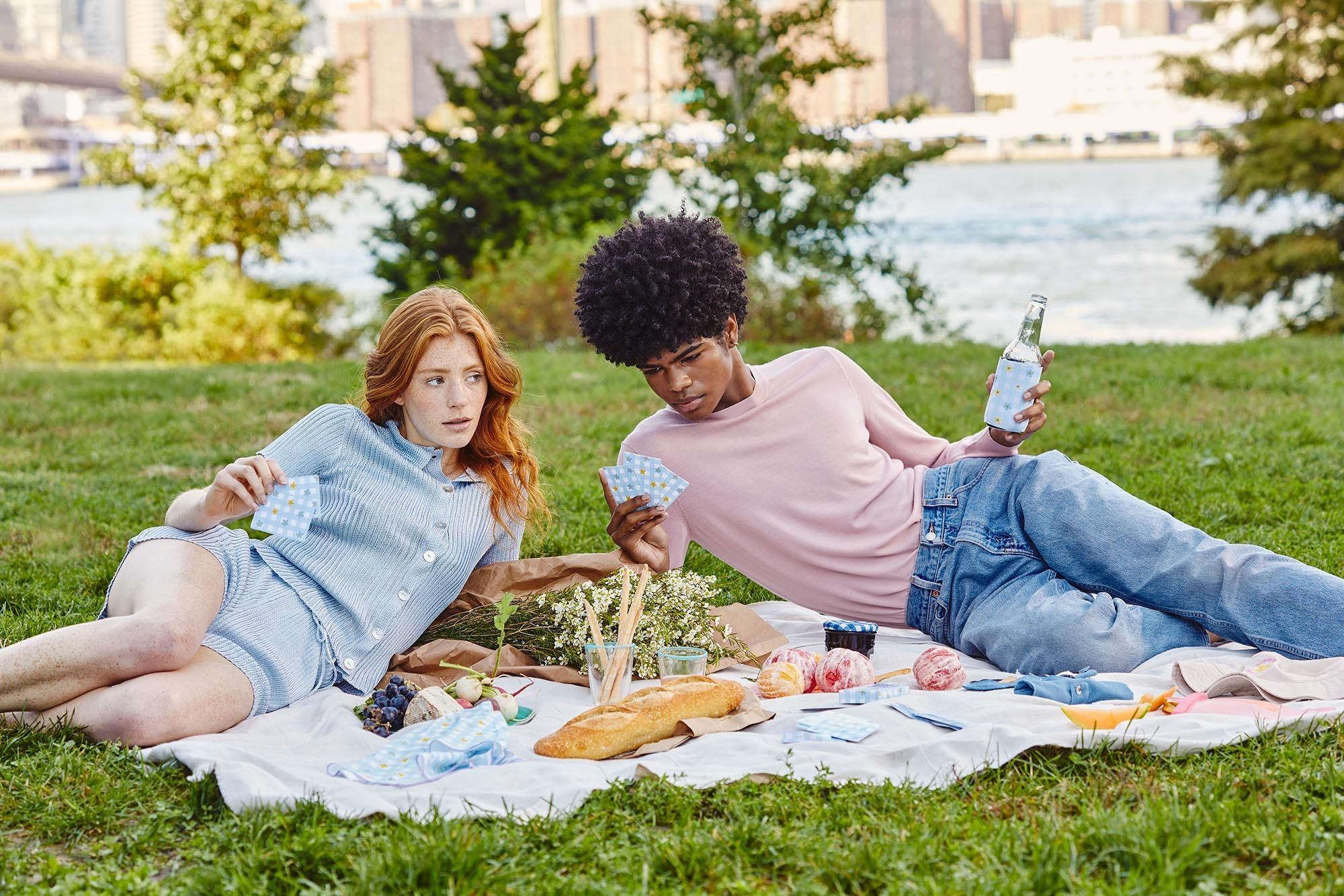 boy and girl playing cards and having a picnic in a park with NYC in background