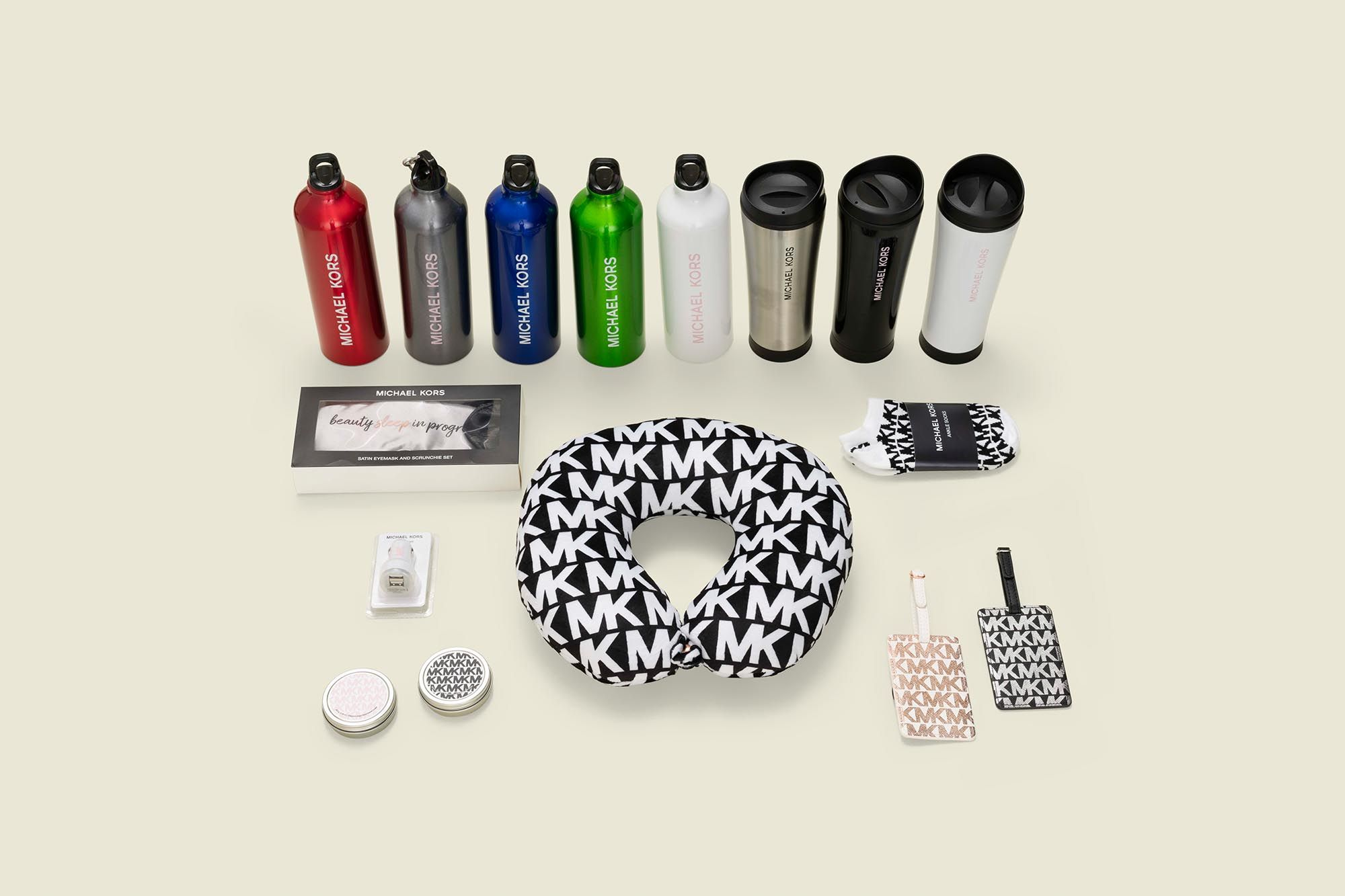 Collection of water bottles, a neck pillow, nah tags, candles, socks, car charger port and sleep mask