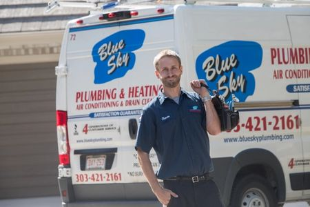 Our skilled HVAC technician smiling while standing in front of one of our company's service trucks in Wheat Ridge, CO