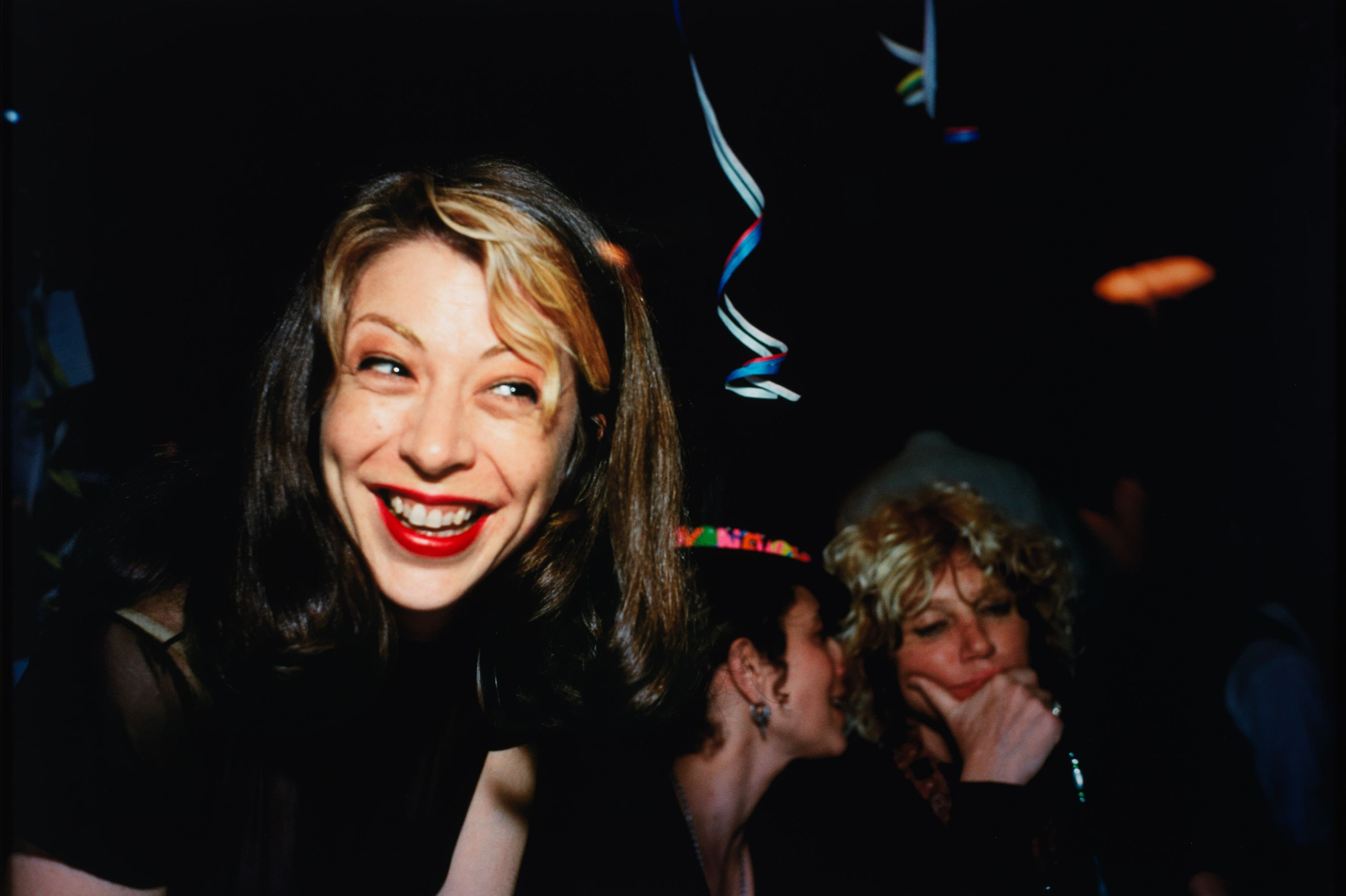 An image of Kathleen with a wide grin, laughing in a bar
