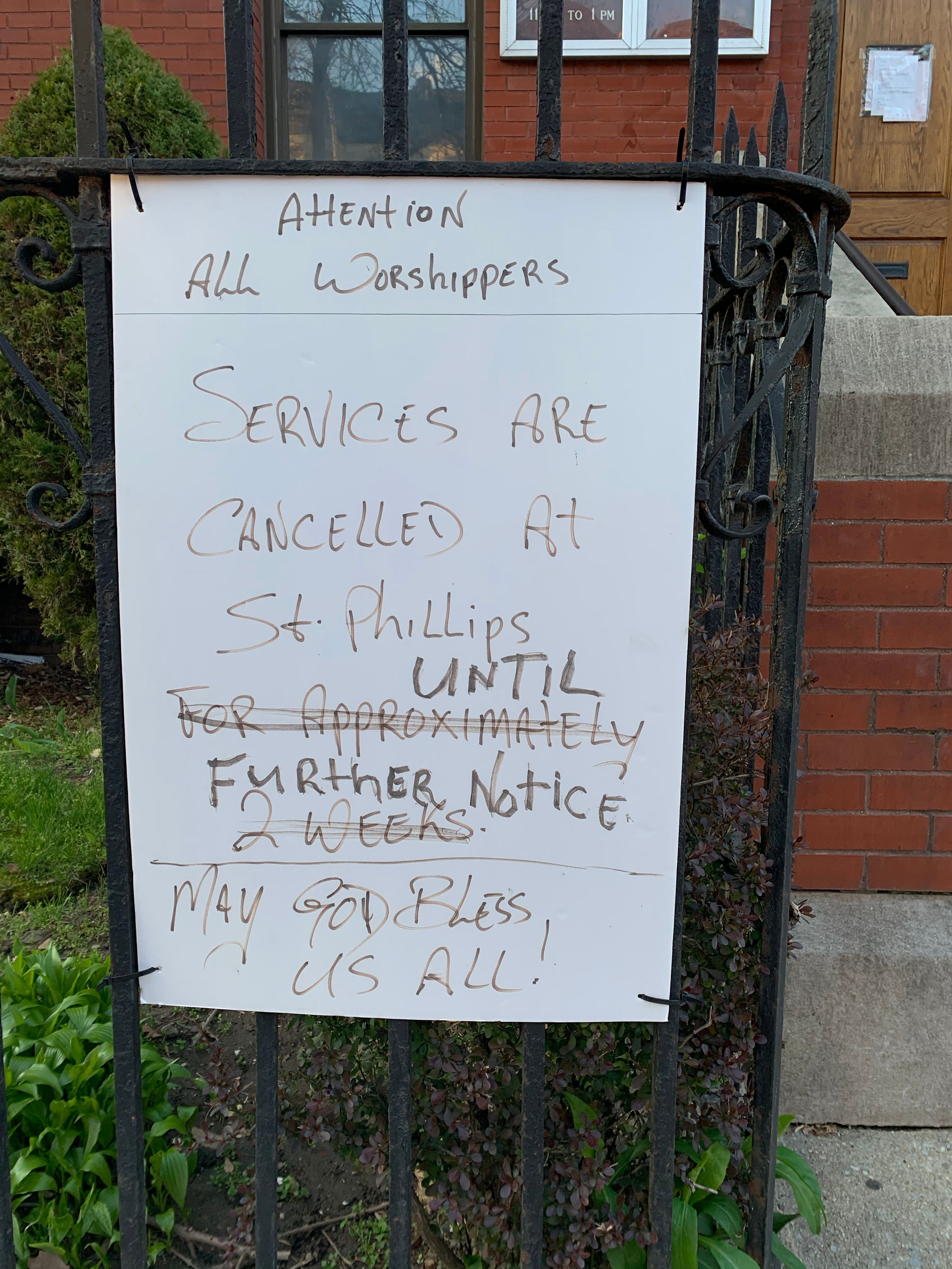 """Hand-written sign taped to a mailbox that reads """"Dear Worshippers, All services canceled until further notice."""""""