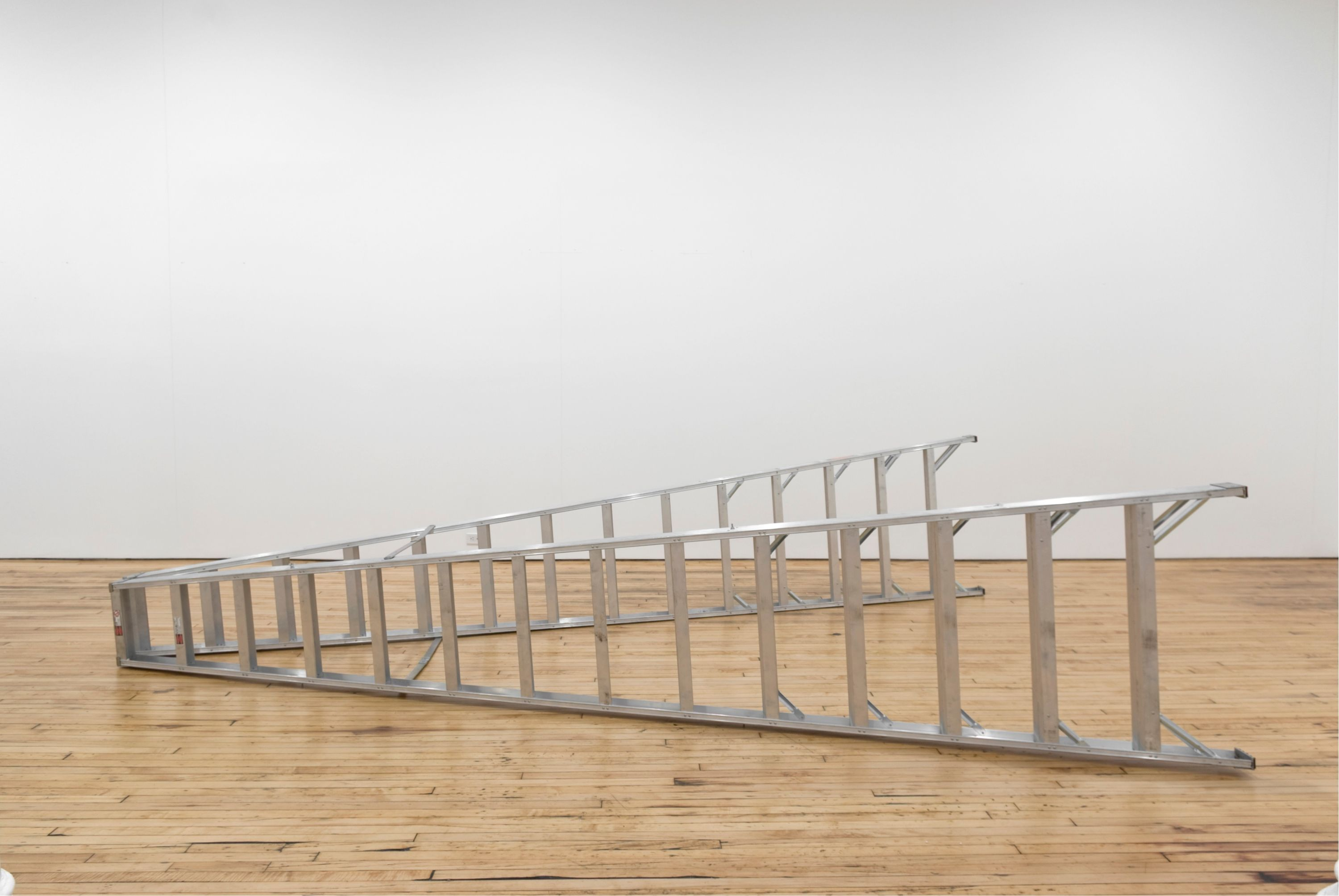Large silver ladder lying on the floor.