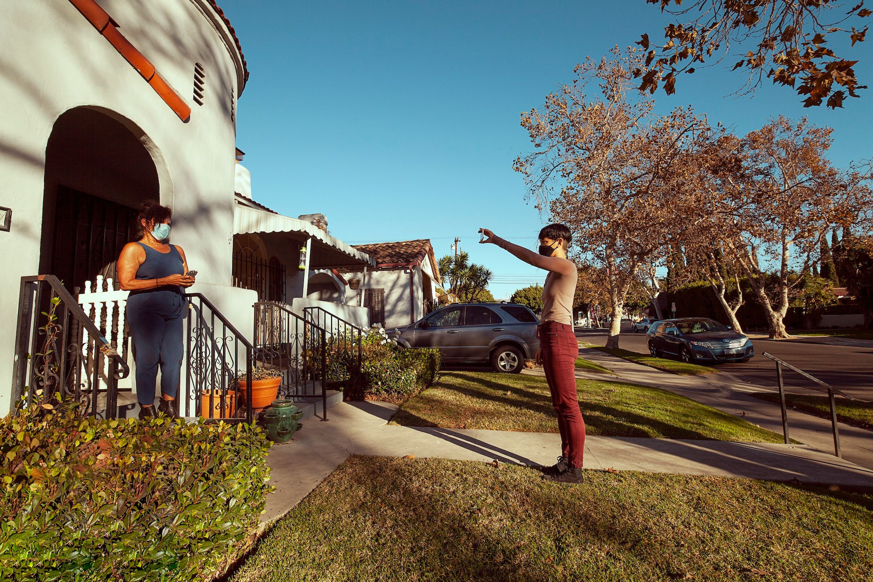 The artist wears red pants and a beige shirt, and stands up straight while holding up her smartphone with an outstretched arm. She faces a residential house, where a woman in a blue tank top stands in the entryway to what appears to be her home. The two women face each other, with a blue sky in the background.