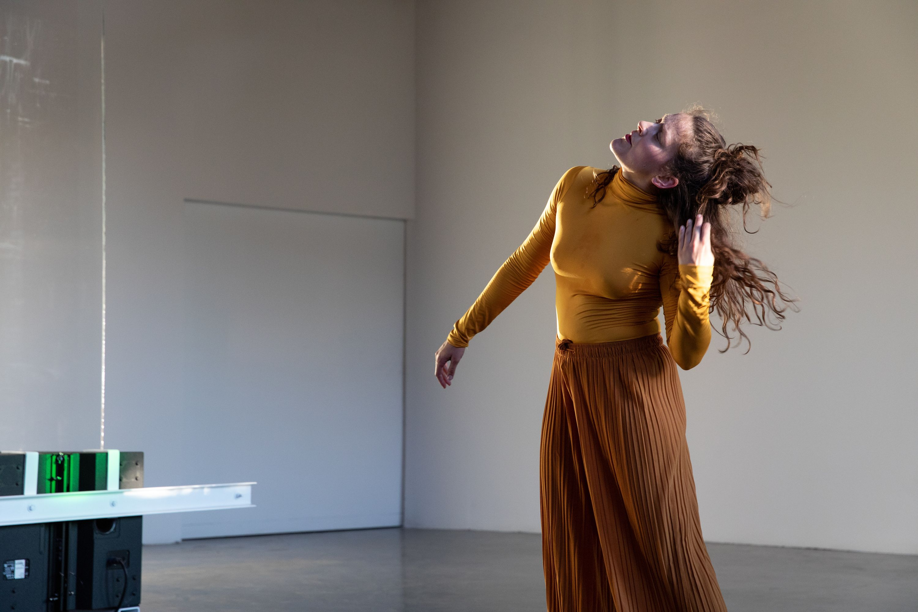 A woman in yellow pulls at her hair, her head craned to her right.