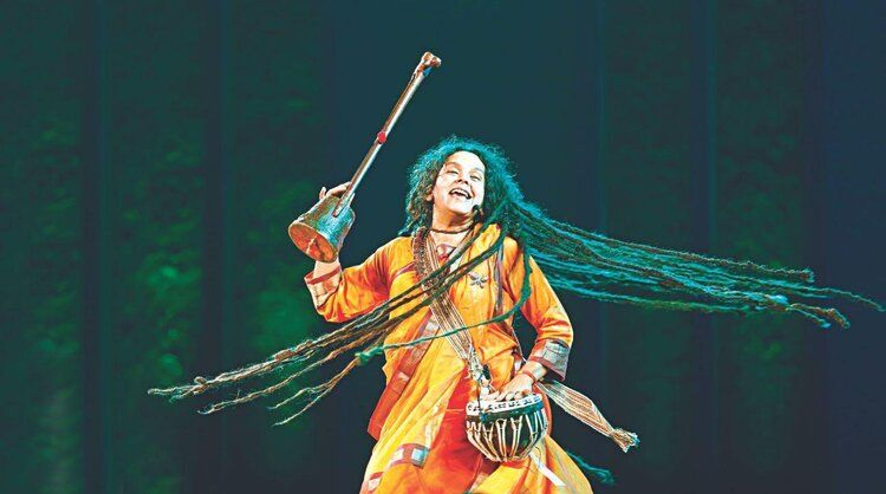 Parvathy Baul, swinging her long dreadlocks while holding a tabla