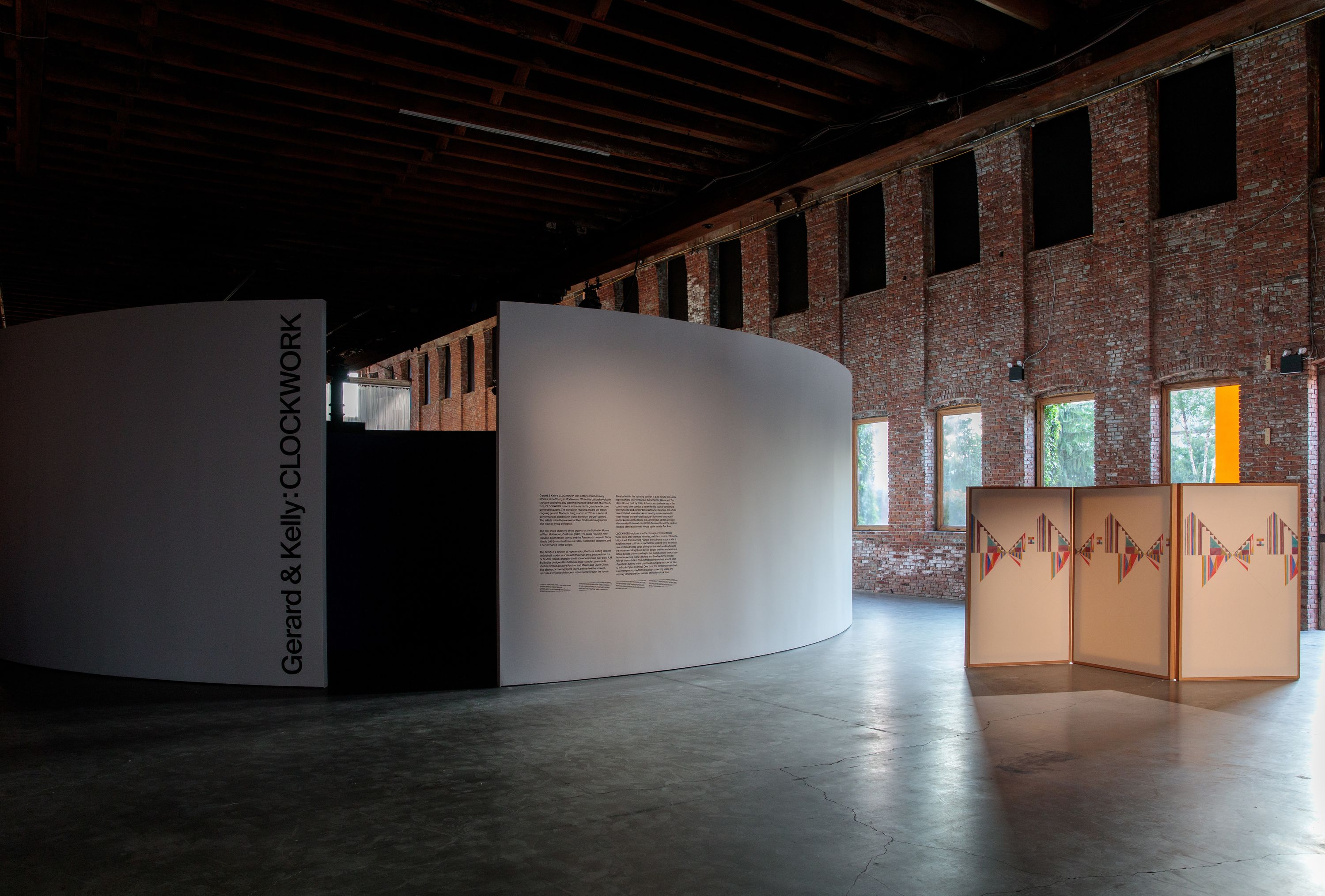 An installation view of the entrance of CLOCKWORK, featuring the entrance to the round-walled video room to the left, and a human-sized folding screen painted in pastels to the right.