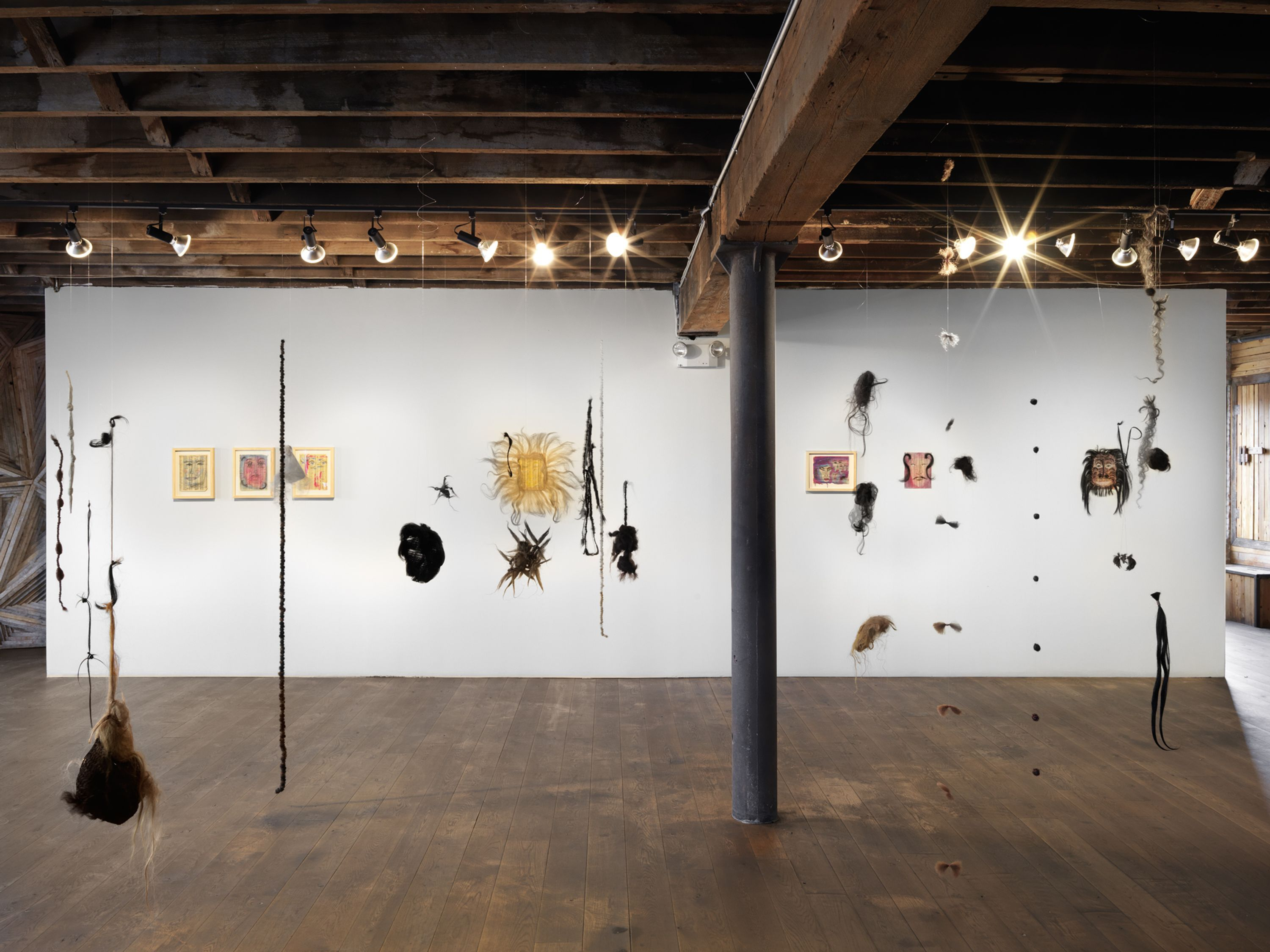 """An installation view of """"Spirits of Manhattan,"""" featuring hanging wigs in Pioneer Works' industrial space"""
