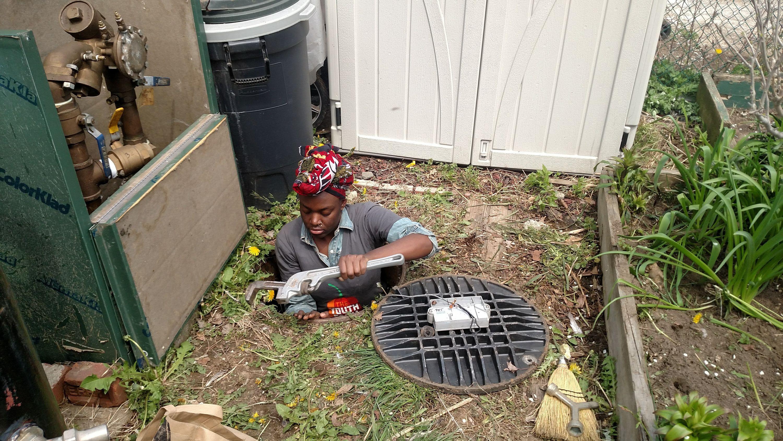 Sawdayah Brownlee performing water systems maintenance in a manhole in a garden, from the Merrick-Marsden Neighbors Association Garden, a BQLT garden, Jamaica, Queens